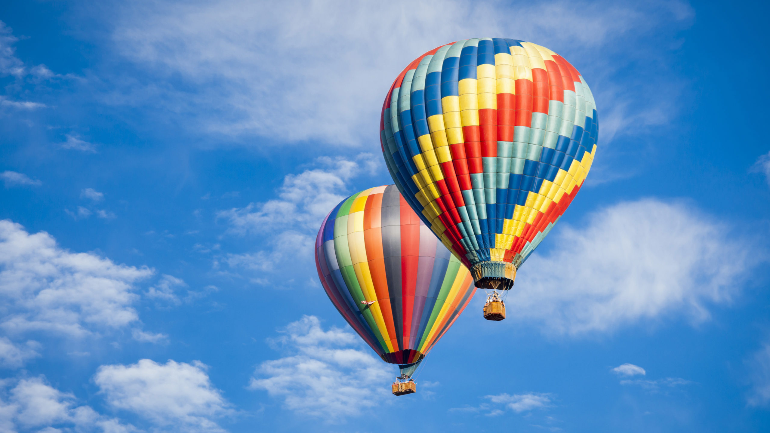 Two colorful hot air balloons floating in blue sky with whispy clouds