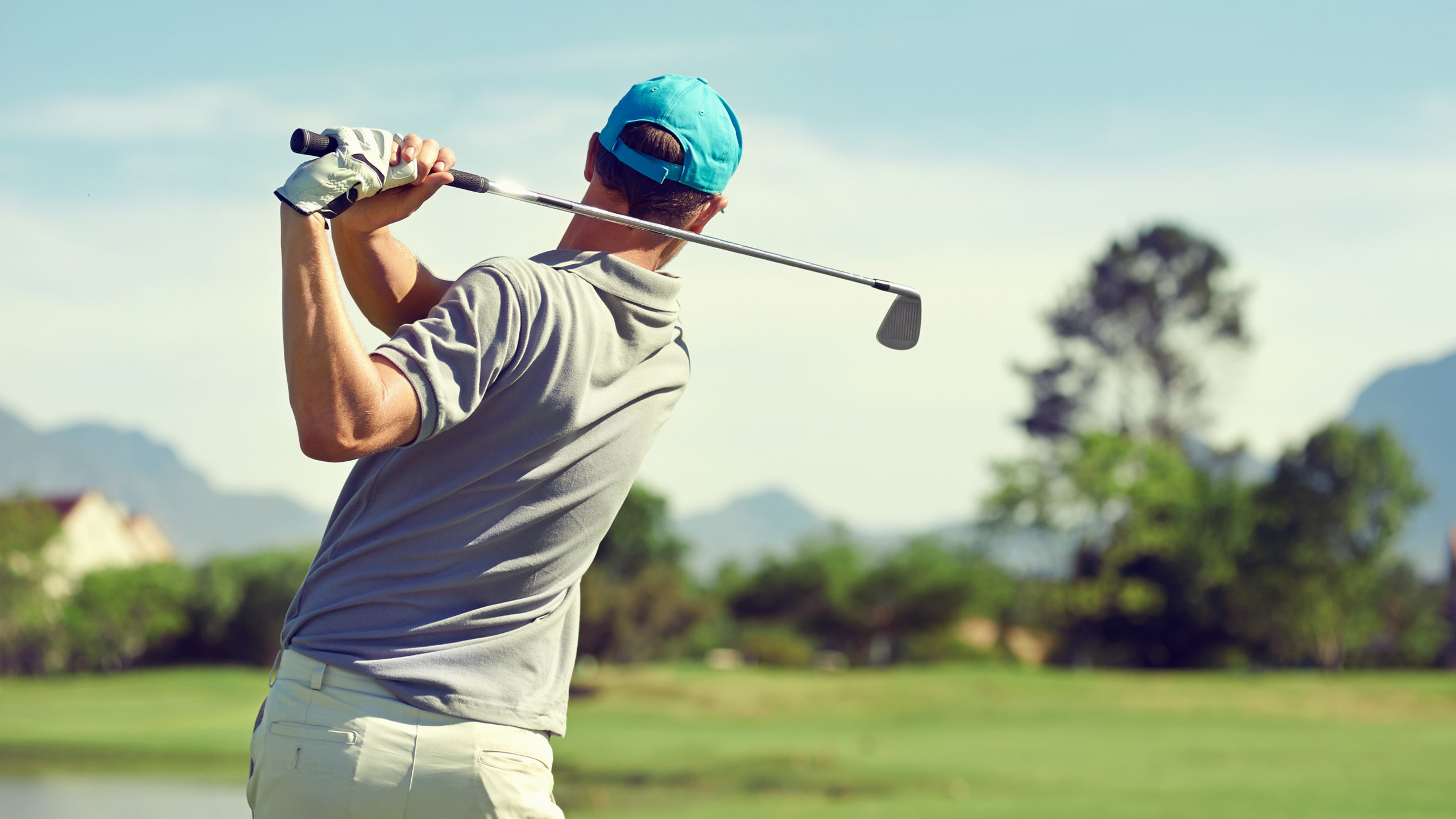 Waist up view of man in golf backswing looking down the fairway