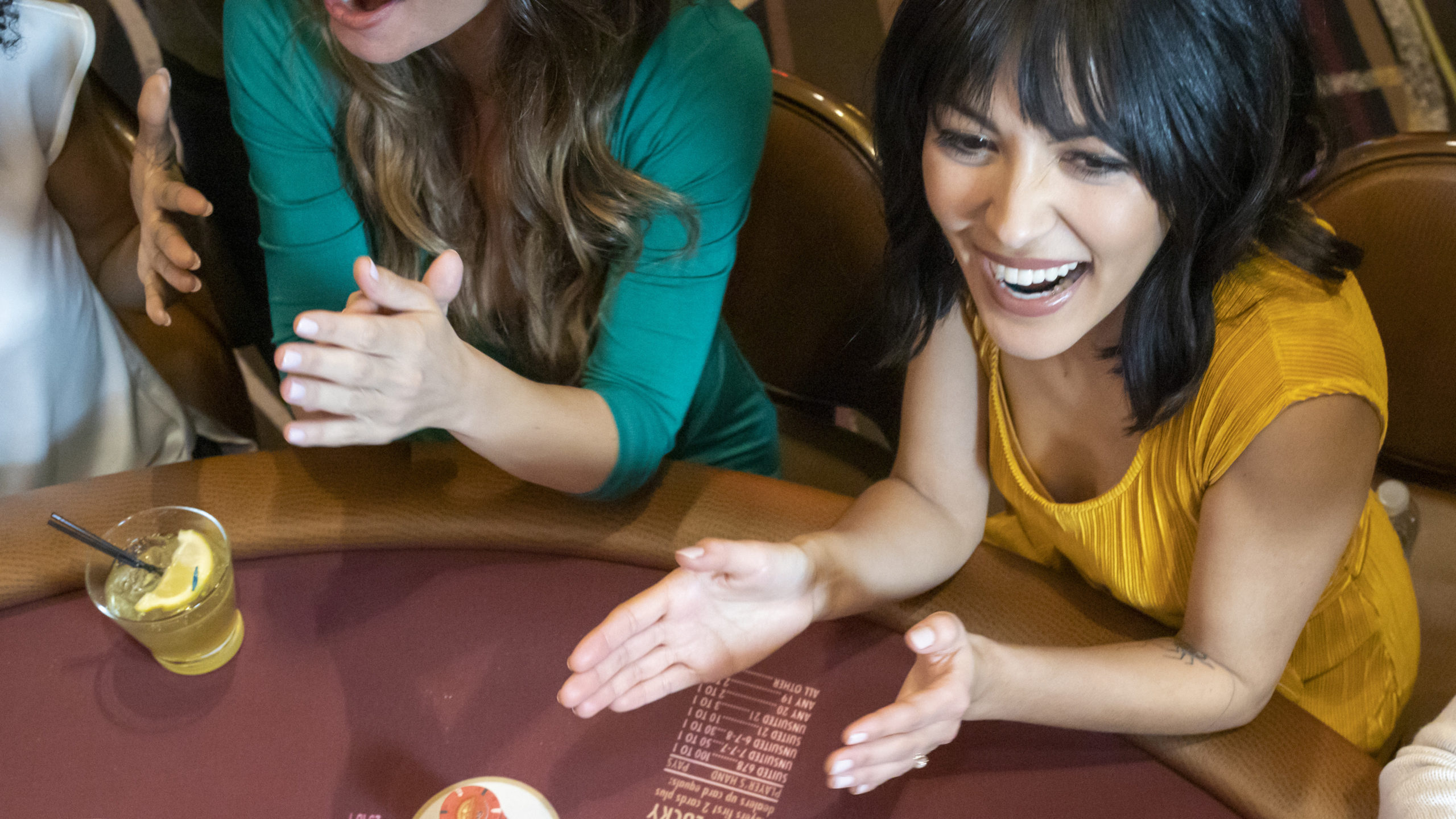 Woman laughing and clapping her hands at a Pai Gow Poker table