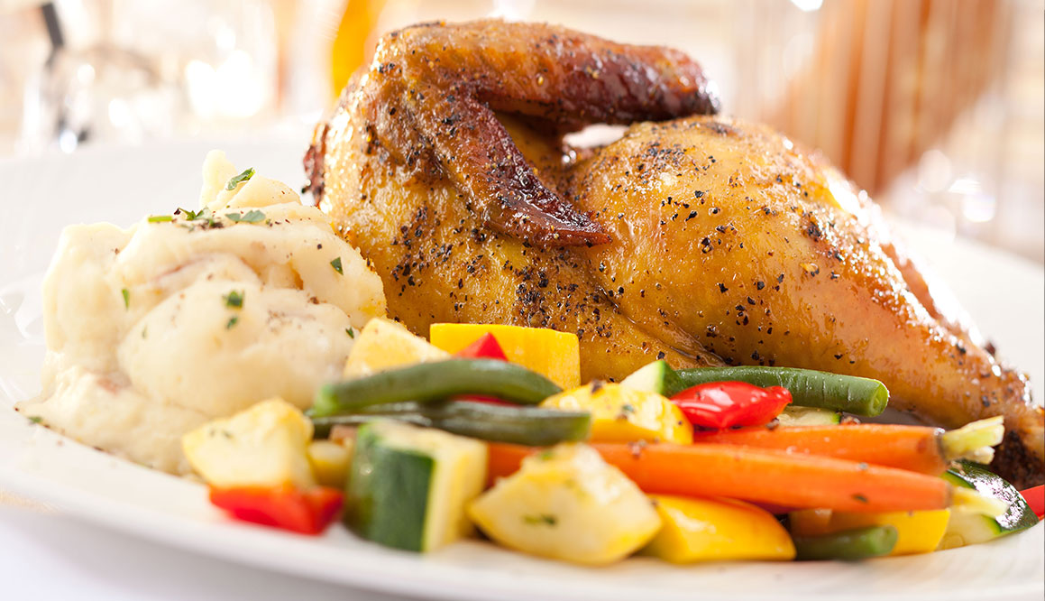 An image of a rotisserie chicken with veggies and mashed potatoes on the side