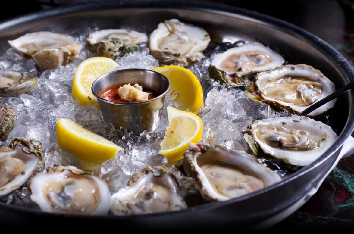 a photo of a plate of oysters on ice with lemons